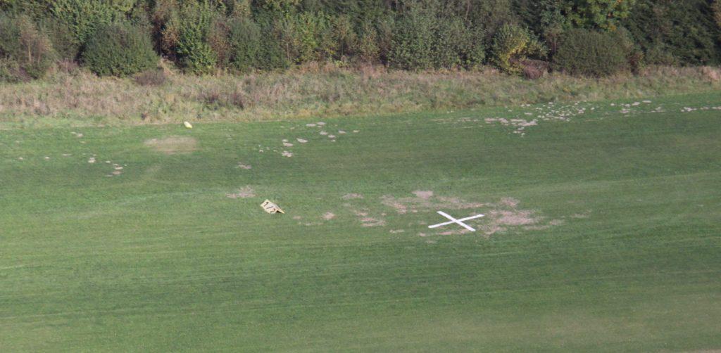 Luftaufnahme der jüngsten Wildschäden. Das weiße Kreuz signalisiert anfliegenden Piloten die Sperrung der Landebahn.